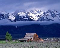Summer storm light illuminating a barn below the Teton Range; Grand Teton National Park, WY