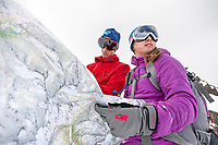 The Ortler Group in northern Italy is a popular region for spring ski touring using the huts for overnights to ski all the many peaks in the mountain group. Two skiers looking at a map in cloudy weather.