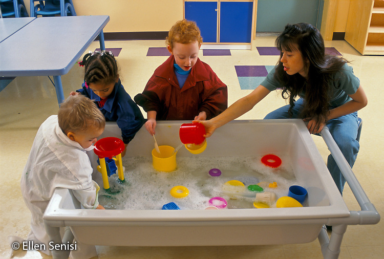MR / Schenectady, New York.Schenectady Day Nursery: private nonprofit daycare.Toddler class / Students and aide (23, Chinese-American / Caucasian) play together at water table. .MR: Rob5, Div1, Hil8, Hoy1, Hoy2                               .PN#:25658                                                     FC#:27916-00118.scan from slide.© Ellen B. Senisi