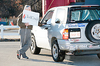 A campaign volunteer speaks to an attendee leaving while taking down campaign signs after Texas senator and Republican presidential candidate Ted Cruz spoke at a town hall at Crossing Life Church in Windham, New Hampshire, on Tues. Feb. 2, 2016. On the vehicle, a number of anti-Clinton and anti-Obama bumper stickers are visible.  The day before, Cruz won the Iowa caucus.