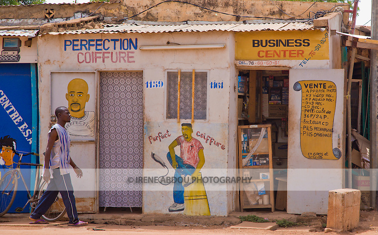 A painting on the wall of the building advertises a barber shop to a mostly illiterate population in Ouagadougou, Burkina Faso.