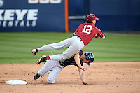 Duke Kinamon #12 of the Stanford Cardinal throws to first base after avoiding Scott Hurst #6 of the Cal State Fullerton Titans during a game at Goodwin Field on February 19, 2017 in Fullerton, California. Stanford defeated Cal State Fullerton, 8-7. (Larry Goren/Four Seam Images)