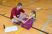 MR / Schenectady, NY. Zoller Elementary School (urban public school). Kindergarten inclusion classroom. Gym teacher helps student hold her knees down as student uses teacher-made equipment to test student flexibility. This is part of his students' yearly assessment of their physical education skills. MR: Mel16, Stu1. ID: AM-gKw. © Ellen B. Senisi.