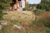 Buffalo grass (Buchloe dactyloides) meadow, naturalistic lawn substitute, as extension of back patio (portale) with Little Bluestem and Junipers; garden design by Judith Phillips