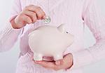 USA, Illinois, Metamora, Child's (10-11) hand putting money into piggy bank