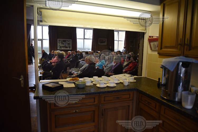 The audience, seen through the kitchen hatch, with tea and digestive biscuits laid out, during a public meeting in Cliffsend Village Hall, near Ramsgate, Kent.