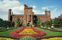 A View in Fall of the main old building of the Smithsonian Institution, with the manicured flowers, grass and grounds in front. Blue sky and clouds behind. Old building, brownstone,. Washington D.C. District of Columbia, United States Capitol Mall.