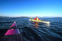 Male paddler in yellow kayak and yellow PFD paddling in San Juan Islands, Sea Kayaking the San Juan Islands, WA.