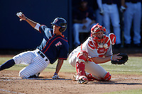 Tanner Lubach #8 of the Nebraska Cornhuskers waits for the throw as Matt Orloff #2 of the Cal State Fullerton Titans slides past to score during a game at Goodwin Field on February 16, 2013 in Fullerton, California. Cal State Fullerton defeated Nebraska 10-5. (Larry Goren/Four Seam Images)