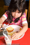 Preschool 3-5 year olds girl pouring own milk at meal hot lunch provided by Headstart program vertical