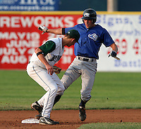 Southwest Michigan Devil Rays Matt Devins looks to tag Michael Hollimon on a steal attempt during a Midwest League game at C.O. Brown Stadium on July 14, 2006 in Battle Creek, Michigan.  (Mike Janes/Four Seam Images)