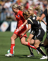 26 April 2009:  Allie Long of the Washington Freedom dribbles the ball away from FC Gold Pride defenders during the game at Buck Shaw Stadium in Santa Clara, California.   Washington Freedom defeated FC Gold Pride, 4-3.