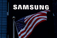 NEW YORK, NEW YORK - MARCH 04: A USA flag waves in front a Samsung logo in Times Square on March 04, 2021 in New York. Samsung Electronics Co Ltd is considering four sites en United States, for a new $17 billion chip plant. (Photo by Emaz/VIEWpress)