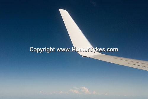 Wing of an airplane, deep blue sky, cumulus nimbus clouds. Anywhere 2006
