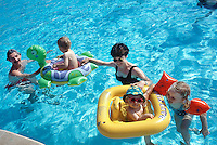 """Spain. Mallorca in the Balearic islands. Colonia Sant Jordi. A father, a mother and their children play in the swimming pool of the """"Don Leon"""" hotel. Inflatable boat and turtle. Inflatable safety swimmimg device for children. © 1999 Didier Ruef"""