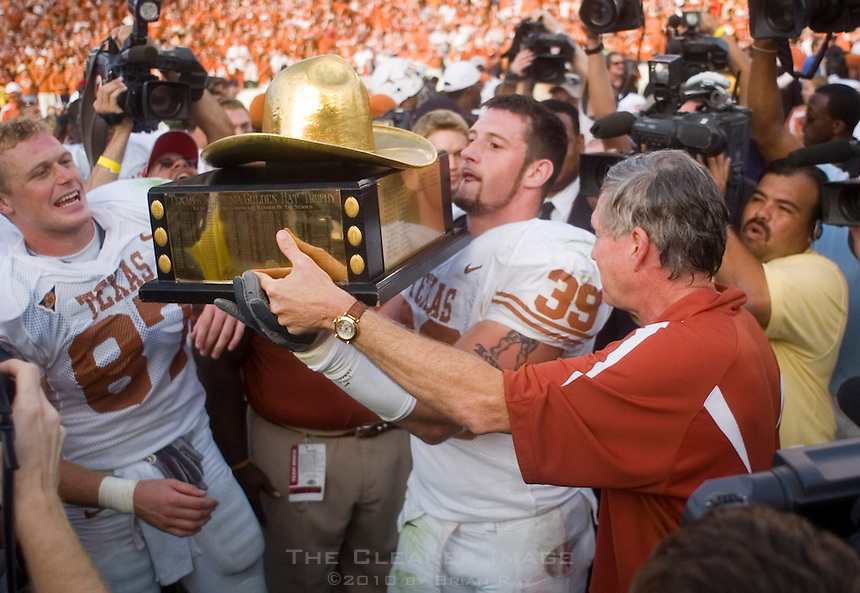 07 October 2006: Texas head coach Mack Brown hands the Golden Hat Trophy to defensive end Brian Robison (#39) after the Longhorns 28-10 victory over the University of Oklahoma Sooners at the Cotton Bowl in Dallas, TX.