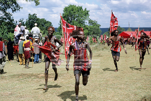 Lolgorian, Kenya. Eunoto coming of age ceremony; moran Maasai warriors running with non-tribal Africans with pick-up.