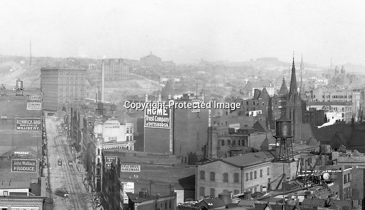 Pittsburgh PA:  View of Liberty Avenue from the top of the Empire Building.  Pennsylvania Railroad's Union Station in the background.<br /> <br /> Building Advertising for the following companies; Lyle Brothers Hardware, Home Trust Company of Pittsburgh, John Wallace Produce, Renwick Brothers Wholesale Millinery, J.C. Lindsay Hardware Company, Monongahela National Bank