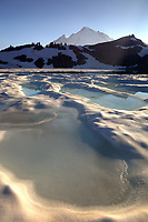 Pool of melt water on iced over 14-Goat Lake at sunset, Mount Baker in background, Ptarmigan Ridge, Mount Baker National Recreation Area, Washington Cascades, USA