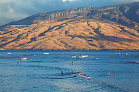 First light of the day hits the West Maui Mountains while surfers enjoy some waves at Cove Park, Kihei, Maui.