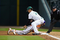 Dominick Cammarata (24) of the Charlotte 49ers applies a late tag as Kyle Wilkie (10) of the Clemson Tigers dives back into first base at BB&T BallPark on March 26, 2019 in Charlotte, North Carolina. The Tigers defeated the 49ers 8-5. (Brian Westerholt/Four Seam Images)