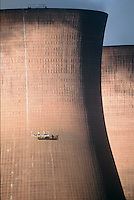 Men cleaning cooling towers of power station.