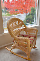 Wicker rocking chair with front window fall view and rain. Wilsonville. Oregon