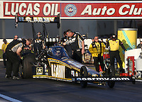 Feb. 17, 2013; Pomona, CA, USA; NHRA crew chief Mike Green makes an engine adjustment for top fuel dragster driver Tony Schumacher during the Winternationals at Auto Club Raceway at Pomona. Mandatory Credit: Mark J. Rebilas-