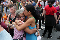 ANDREW SHURTLEFF/DAILY PROGRESS PHOTO<br /> Abby Guskin (right) gives a hug to Katrina Turner (left) as police remove the barricades from Fourth and Water Street signaling the end of  the mall lockdown Sunday on the anniversary of August 12th.