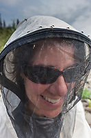 Woman wears mosquito headnet for protection.