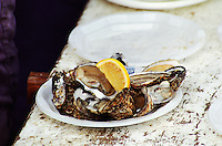 In a street food market in Bordeaux on the Quai des Chartrons: a serving of freshly opened oysters with a slice of lemon on a paper plate on a wooden bench, a quick lunch. Bordeaux Gironde Aquitaine France Europe  Bordeaux Gironde Aquitaine France Europe