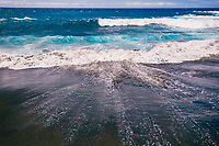 Strong waves break and recede on a remote black sand beach in Ocean View, Hawai'i Island.
