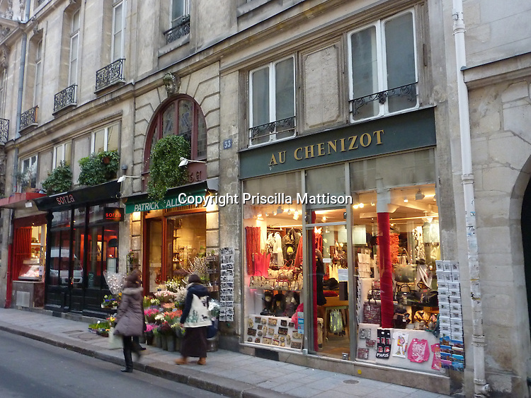Paris, France - February 2, 2011:  Shoppers walk in front of brightly lit storefronts on Ile St. Louis in Paris.