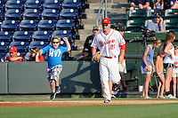 A youth ballplayer is excited to run onto the field with right fielder Nick Longhi (21) of the Greenville Drive before a game against the Charleston RiverDogs on Monday, June 29, 2015, at Fluor Field at the West End in Greenville, South Carolina. Longhi is the No. 27 prospect of the Boston Red Sox, according to Baseball America. Greenville won, 4-2. (Tom Priddy/Four Seam Images)