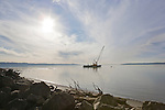 A barge mounted crane works on placing rock for an artificial reef at Saltwater State Park, Washington.  The reef will provide habitat attracting marine life for scuba divers.