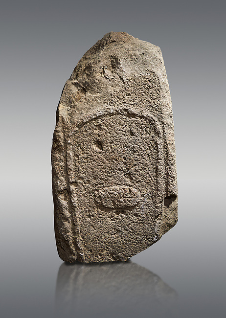 Late European Neolithic prehistoric Menhir standing stone with carvings on its face side. Excavated from Amassed VII, Allai.  Menhir Museum, Museo della Statuaria Prehistorica in Sardegna, Museum of Prehoistoric Sardinian Statues, Palazzo Aymerich, Laconi, Sardinia, Italy. Grey background.