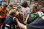 CHAD PILSTER •Hays Daily News<br /> <br /> Logan Hook, left, 1, kisses one of the foal's as Gage Hallam, right, 4, watches Marion Schmidt, top right right, the owner, tells the kids about the miniature horses on Monday, June 3, 2013, at the Blue Sky Miniature Horse Farm in Hays, Kansas. Hays Rec took a group of kids out to the farm to learn about some of the smallest horses in Kansas.