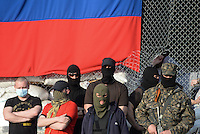 Hooded Pro Russian activists stand in front of the Flag of the Donetsk People Republic in the the city hall. Slavyansk city. Donetsk region.