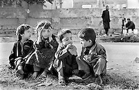 Afghan children eat old bread handed out by a local bakery  in war-torn Kabul onThursday,  July 4, 2002.
