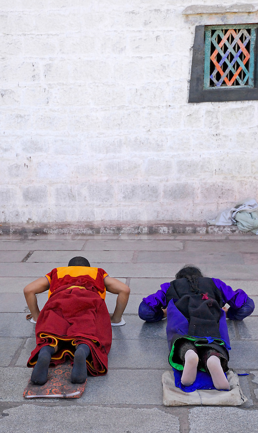 Buddhist monk and pilgrim prostrating outside the 7th century Jokhang Temple during Saga Dawa festival, Lhasa, Tibet.