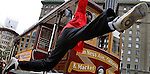A man hangs off a San Francisco cable car at Union Square in San Francisco, California.