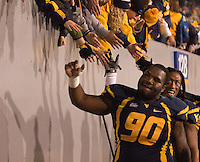 WVU players Shaq Rowell (90) and Bruce Irvin celebrate with fans. The WVU Mountaineers beat the Pitt Panthers 21-20 at Mountaineer Field in Morgantown, West Virginia on November 25, 2011.