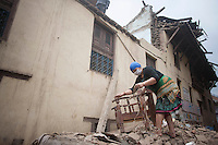 A woman collects items from her destroyed house in Shanku near Kathmandu, Nepal. May 9, 2015
