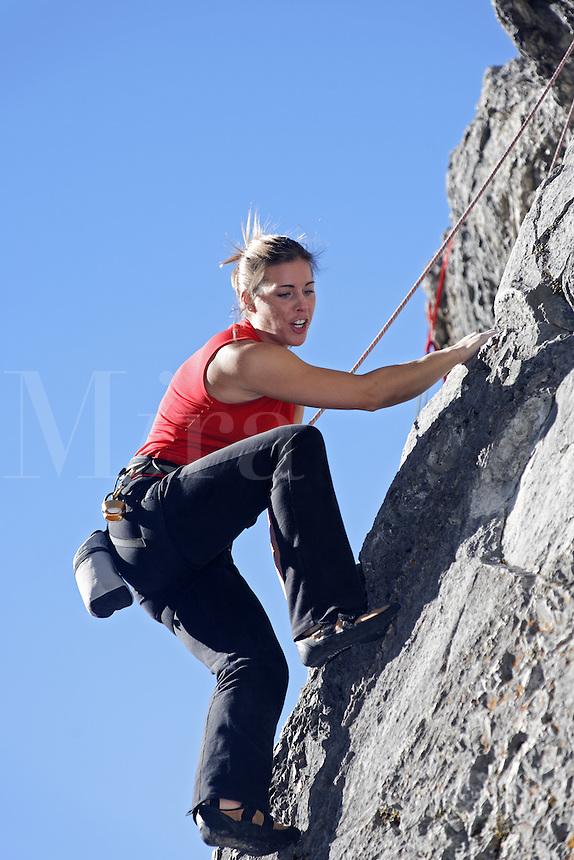 Female climber on rock face against blue sky, Banff, Banff National Park, Alberta, Canada