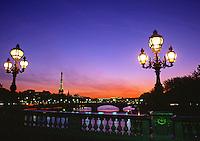 Streetlights glow at twilight on a bridge spanning the River Seine. Paris, France.