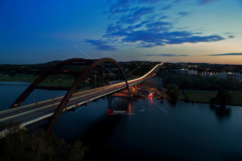 Night falls on the 360 Bridge as cars streak by in Austin, Texas