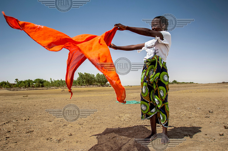 A woman dries a piece of cloth in the wind in the town of Gao. /Felix Features