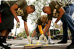 (L to R) Anthony Randolph, Kyle Singler and Gary Johnson paint the 3-point line on a basketball court in New York City as part of their volunteer service on August 31, 2006.  The players were in town for the Elite 24 Hoops Classic, which brought together the top 24 high school basketball players in the country regardless of class or sneaker affiliation.
