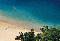 People playing on white sand beach and clear blue water, Waimea Bay, Oahu, Hawaii