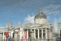Sidewalk reflections after a brief shower in Trafalgar Square, London, England